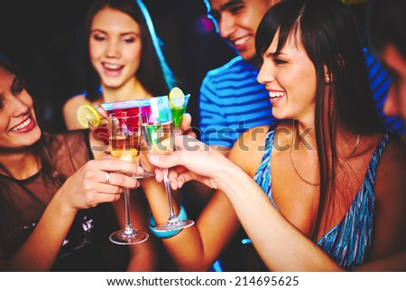 Portrait of joyful friends toasting at birthday party - stock photo