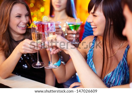 Portrait of joyful friends toasting at birthday party with focus on laughing girl