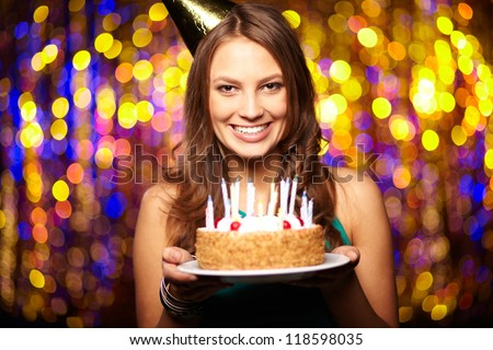 Portrait of joyful girl holding birthday cake and looking at camera at party - stock photo