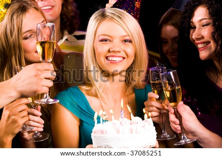 Portrait of joyful girl holding birthday cake and smiling at camera at party