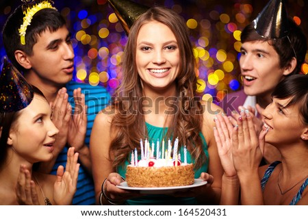 Portrait of joyful girl holding birthday cake with friends near by at party - stock photo