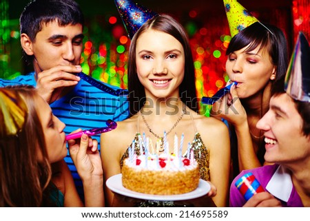 Portrait of joyful girl with birthday cake looking at camera at party with her friends near by - stock photo