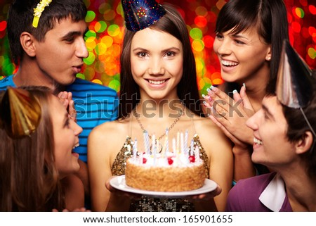 Portrait of joyful girl with birthday cake surrounded by friends at party - stock photo