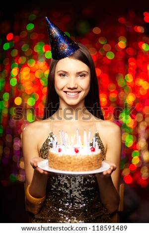 Portrait of joyful girl with cake looking at camera at birthday party - stock photo