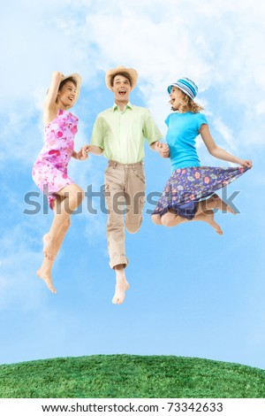 Portrait of joyful girls in jump holding happy man by hands with blue sky on background