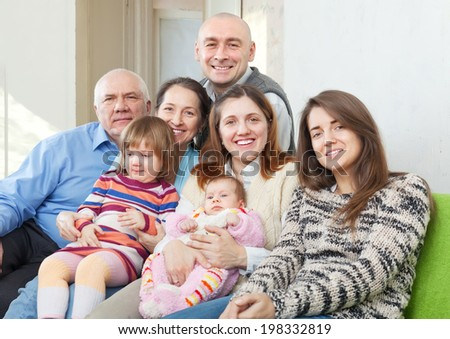 Portrait of joyful grandparents with  children and grandchildren in home interior - stock photo