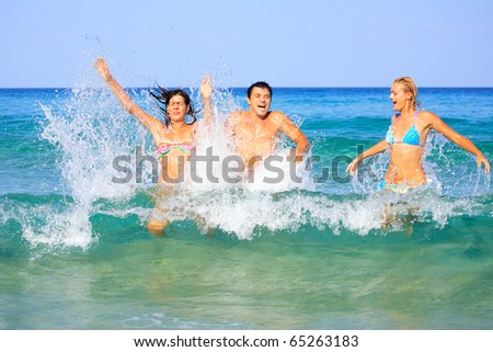 Portrait of joyful group of people having fun in the sea and laughing - stock photo