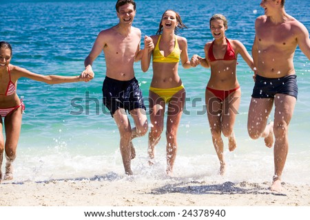 Portrait of joyful group of teens having fun on seashore and laughing