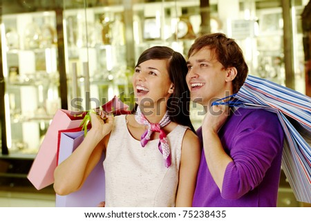 Portrait of joyful husband and wife looking at some goods in the mall - stock photo