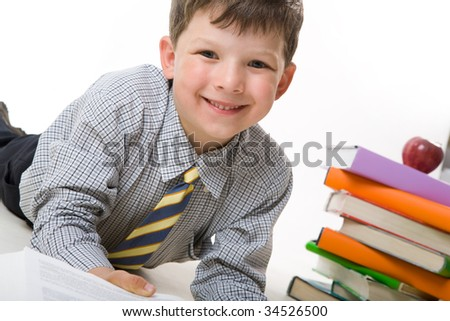 Portrait of joyful kid looking at camera with stack of books and red apple on background - stock photo