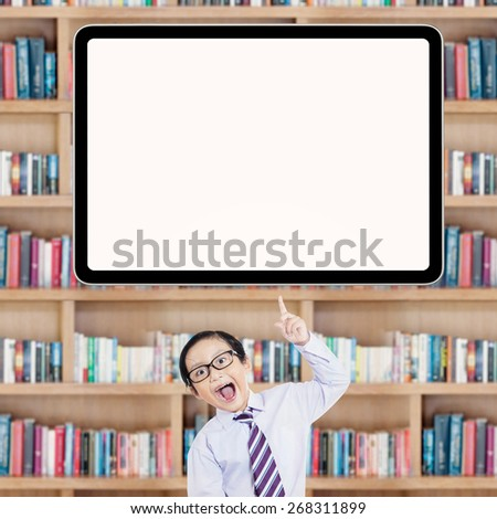 Portrait of joyful little student pointing at empty whiteboard in the library - stock photo
