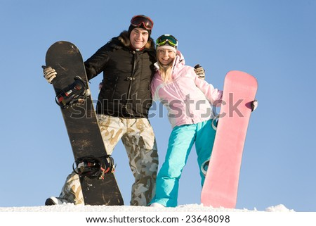 Portrait of joyful man and woman standing on snow with boards in hands