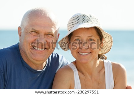 Portrait of joyful mature couple against sea and sky - stock photo