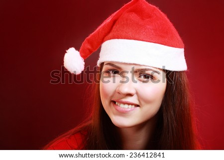 Portrait of joyful pretty woman in red santa claus hat laughing. Beautiful girl looking happy and excited. Happy Christmas and New Year holidays full of fun. - stock photo