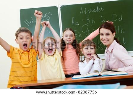 Portrait of joyful schoolchildren showing gladness with their teacher near by - stock photo