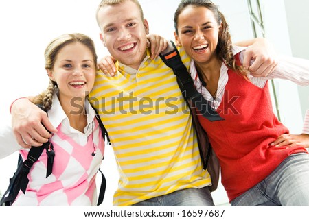 Portrait of joyful teens embracing and looking at camera with laugh - stock photo