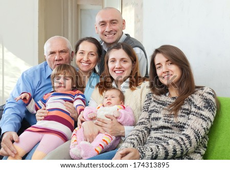 Portrait of  joyful three generations family sits on sofa in livingroom