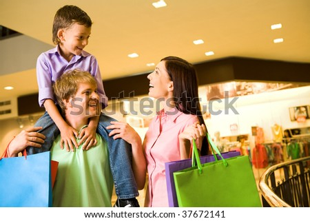 Portrait of joyful woman looking at her son on father?s shoulders in the mall - stock photo