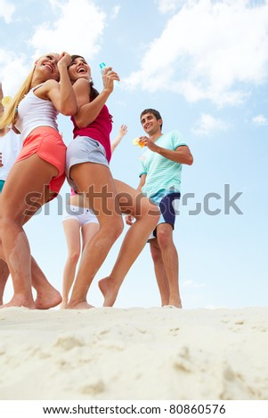 Portrait of joyful young friends dancing at beach party - stock photo