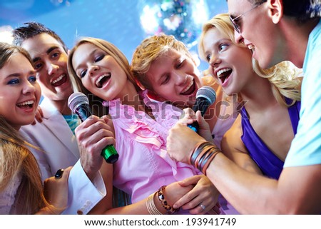 Portrait of joyous friends singing at party together