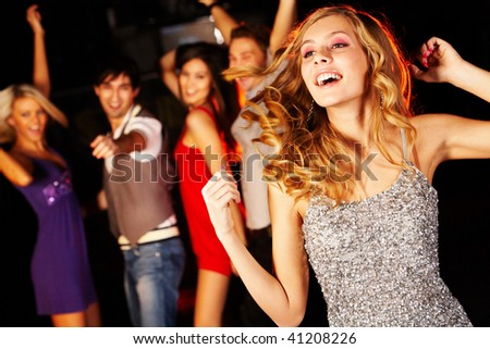Portrait of joyous girl dancing at party on background of happy teens