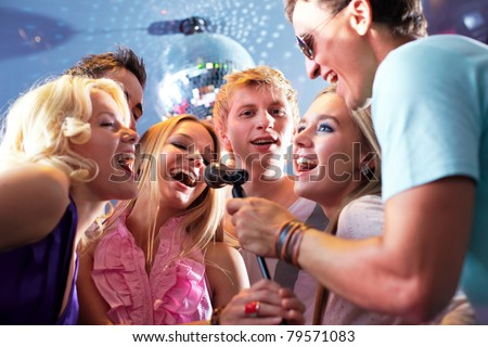 Portrait of joyous guys and girls singing at party in one microphone
