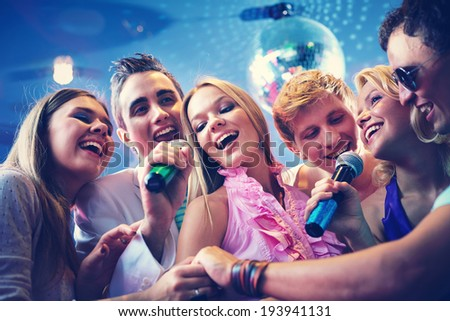 Portrait of joyous guys and girls singing at party together - stock photo