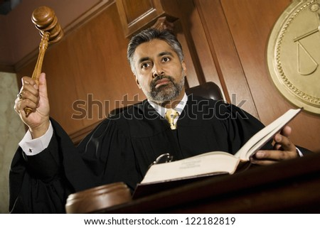 Portrait of judge pounding mallet in courtroom - stock photo