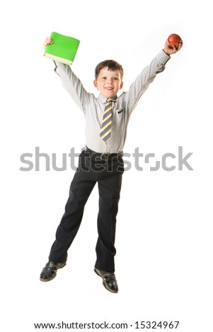 Portrait of jumping boy raising his arms and holding apple and book - stock photo