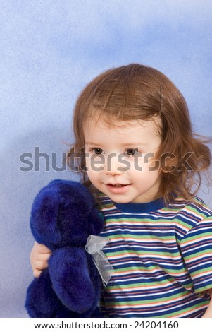 Portrait of kid holding blue Teddy bear (blue background) - stock photo