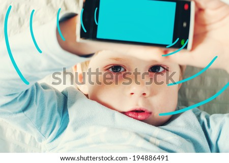 Portrait of Kid with Red Eyes Shows Untoward Influence From Smartphone, toned image with digital graphics - stock photo
