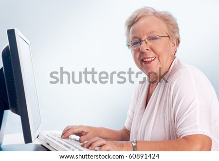 Portrait of kind and friendly woman typing and looking at camera - stock photo