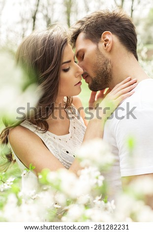 Portrait of kissing couple in the garden - stock photo