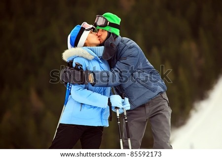 Portrait of kissing couple of skiers - stock photo