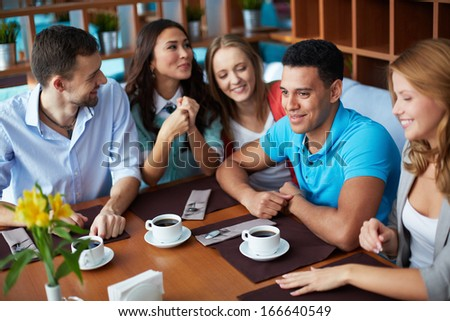 Portrait of large group of teenage friends sitting in cafe - stock photo