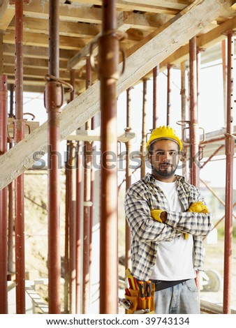 Portrait of latin american construction worker looking at camera with arms folded - stock photo