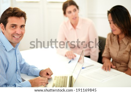 Portrait of latin executive guy smiling at you while working on his laptop and sitting on office conference - stock photo