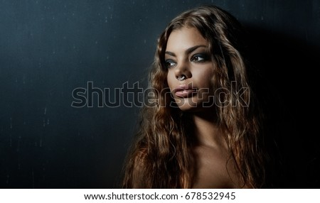 Portrait of latin type sensual woman on dark background.