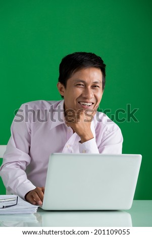Portrait of laughing Asian businessman at his workplace - stock photo