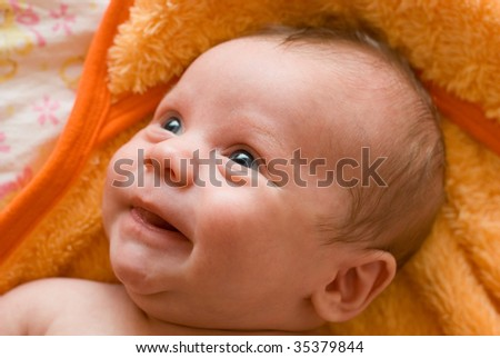 Portrait of laughing baby boy lying on the bed
