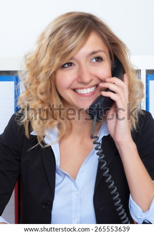 Portrait of laughing blond businesswoman at office at phone - stock photo