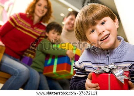 Portrait of laughing boy with nice present on background of his parents and brother - stock photo