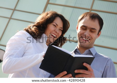Portrait of laughing business partners looking in notepad outside