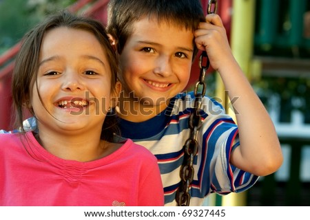 Portrait of laughing children on swing playground outdoors - looking at the camera - stock photo