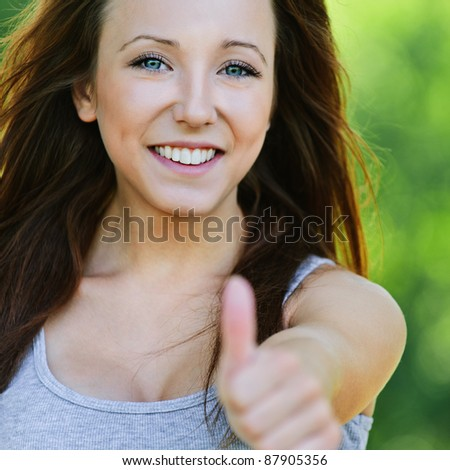 """Portrait of laughing dark-haired teenage girl showing """"thumbs-up"""" sign at summer green park. - stock photo"""