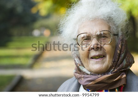 Portrait of laughing elderly woman with golden teeth and grey hait wearing headscarf in park - stock photo