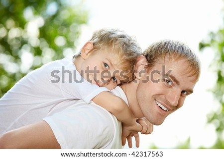 Portrait of laughing father and son piggyback - stock photo