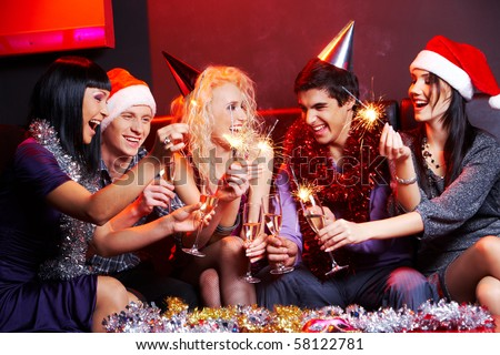 Portrait of laughing friends enjoying xmas lights at new year party - stock photo