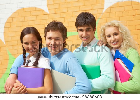 Portrait of laughing friends standing next to each other and looking at camera - stock photo