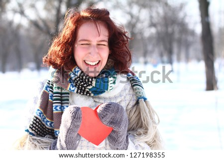 Portrait of laughing girl holding red heart in Winter Park - stock photo